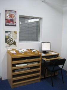 CD's by genre and oversize books and an online catalog terminal by Linda's office