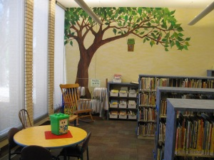 A painted tree provides shade to the portable board book bins in Children's