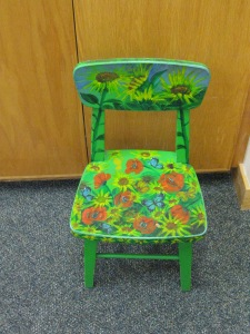 Yet another small painted seat is bedecked with cowboy boots against a bright red background
